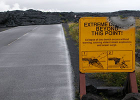 Chain of Craters Road covered with lava beyond this point, as of January 2005; damaged sign warning of dangers of walking onto unstable lava formations