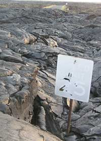 'Speed limit 25' sign with damaged surface sticks out of several feet of solid lava; small patch of yet-to-be-covered pavement in the background