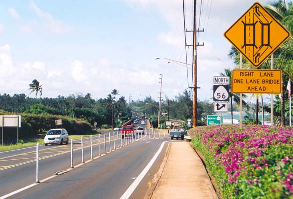 Signs indicating split of two northbound lanes on route 56 at the Wailua River crossing, one lane on the two-lane main bridge, and the other on a separate one-lane bridge