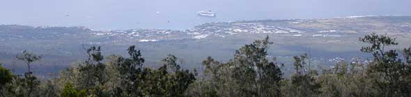 Scenic view of coast around Kailua-Kona, including cruise ship anchored offshore, from Kaloko Drive high on the west slope of the Hualalai volcano
