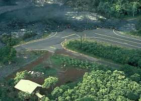 Four-way intersection in Kalapana Gardens, with two legs of intersection covered in lava