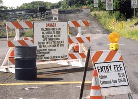 Two signs at beginning of lava viewing road: on sawhorse in foreground, 'Entry fee | Vehicles $5 | Commercial vans $20'; on barricade in background, 'Danger | Volcano fumes are | dangerous to your | health and may be | life threatening | Do not enter this area if | you are a person at risk | Respiratory problems | Heart problems | Pregnant | Infant-young children and elderly'