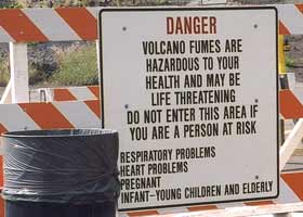 Entry sign on barricade, next to trash can: 'Danger | Volcano fumes are | dangerous to your | health and may be | life threatening | Do not enter this area if | you are a person at risk | Respiratory problems | Heart problems | Pregnant | Infant-young children and elderly'