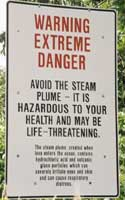 Warning sign: 'Warning | Extreme | Danger | Avoid the steam | plume - It is | hazardous to your | health and may be | life-threatening | The steam plume, created when | lava enters the ocean, contains | hydrochloric acid and volcanic | glass particles which can | severly irritate eyes and skin | and can cause respiratory | distress'
