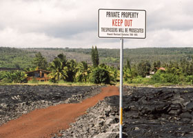 House in background at end of red dirt road through black lava field, behind 'No Trespassing' sign next to road