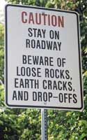 Warning sign: 'Caution | Stay on | roadway | Beware of | loose rocks, | earth cracks, | and drop-offs'