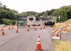Wide view of tollbooth for lava viewing road, with trailer on left and sawhorses and orange cones narrowing two lanes of pavement to one approaching booth