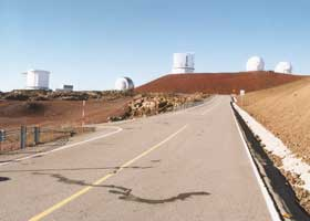 Junction with side road, with five telescopes atop summit in the background