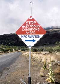 'STOP Hazardous Conditions Ahead' sign, directing travelers to get information at the visitor center