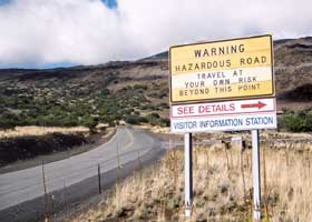 Sign: 'Warning Hazardous Road | Travel At Your Own Risk Beyond This Point'; 'See Details' at Visitor Information Station