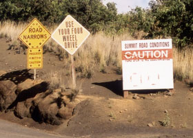 Three warning signs: 'Road Narrows | Proceed With Caution'; 'Use Your Four-Wheel Drive'; and 'Summit Road Conditions: CAUTION | Road Open to All Observatories'