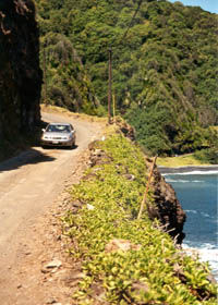 Narrow, barely paved cliffside road high above the ocean, with pebbles in road and no guardrails
