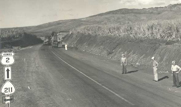 Primary and secondary route markers for wartime route system on Oahu, alongside road with sailors standing alongside and trucks in the background